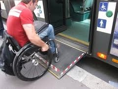 man in a wheelchair getting onto a bus with a ramp fitted to the door